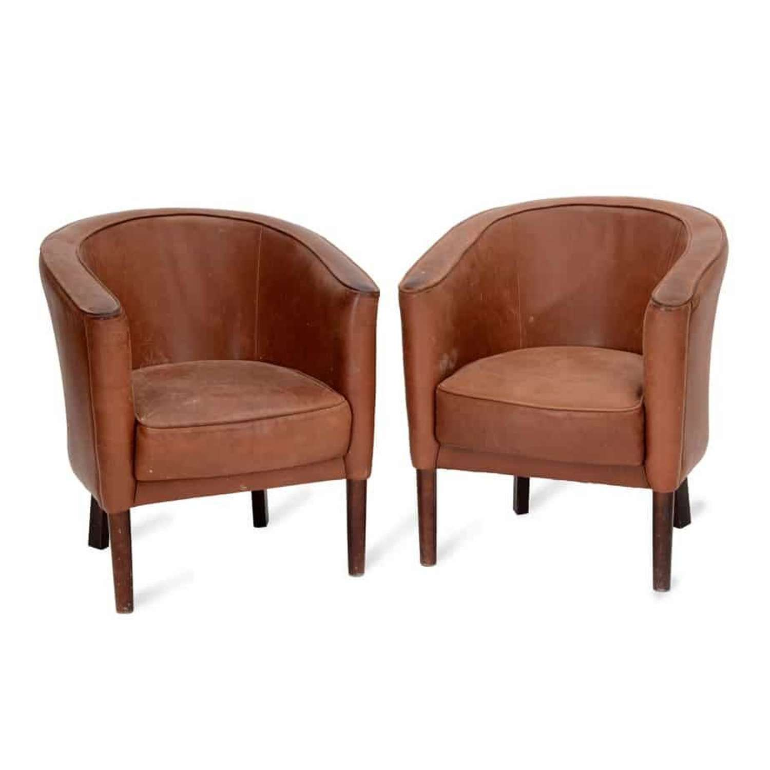 A pair of tan leather tub chairs by Heal's
