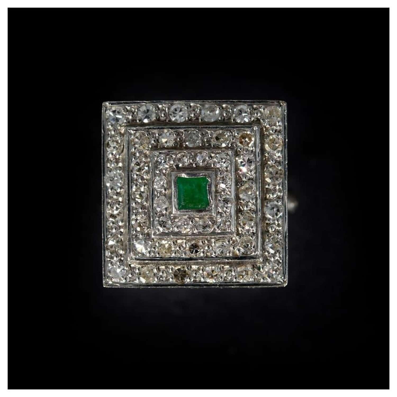 A stylish emerald and diamond panel ring