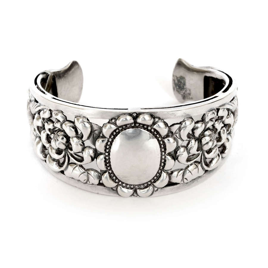 A Victorian silver cuff with birds and flowers.